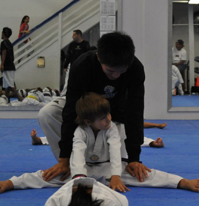 Mr. Manny Reyes helps Ty with stretching technique at OTC